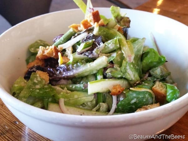 white bowl with green lettuce and pieces of asparagus