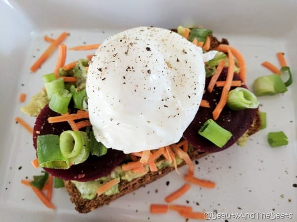 A large poached egg on top of green onions, sliced red beets, grated carrots and mashed avocado on a white square plate