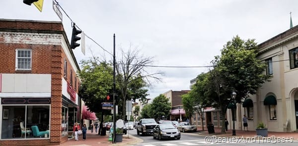 a street corner in downtown Fredericksburg with a brick building and an antique chop on the corner