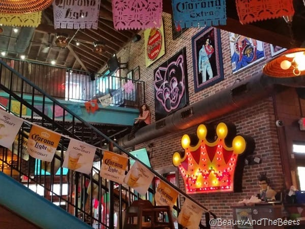 giant room with a wrought iron staircasr in the center with beer banners Elvis pictures and a giant lighted crown on the wall