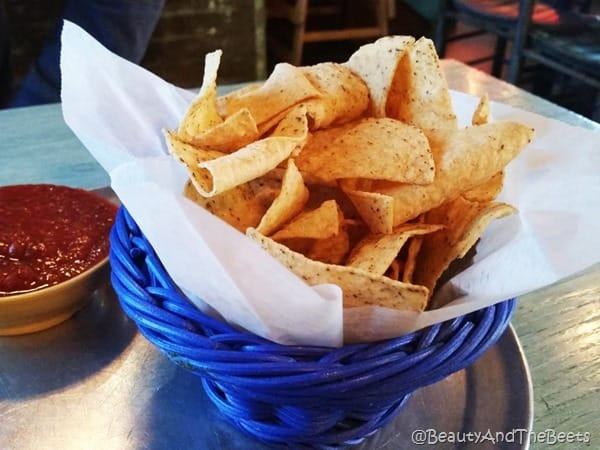 blue basket filled corn tortilla chips with a small yellow bowl with red salsa