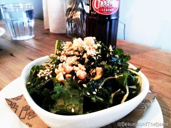 white bowl with kale salad sprinkled peanuts and a bottle of Cheerwine behind it