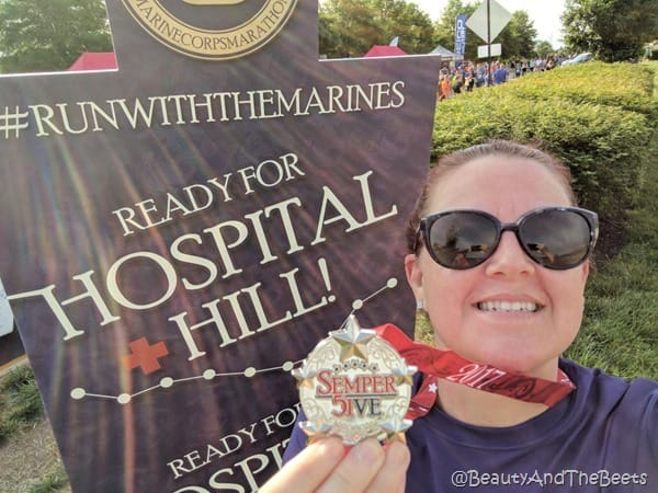 the author with the Semper Five Miler medal in front of a large sign that reads ready for hospital hill