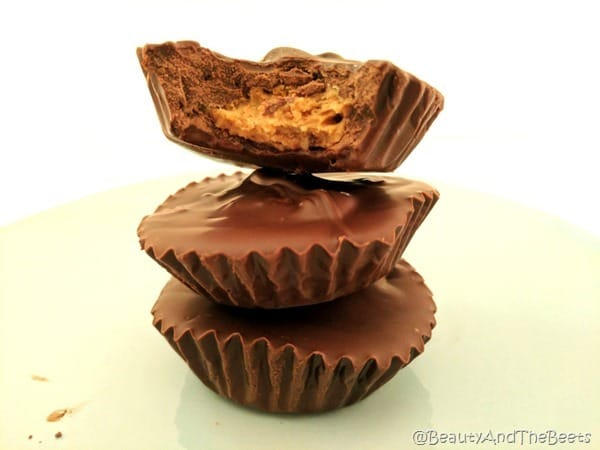 A stack of three peanut butter cups with a bite out of the top cup
