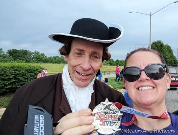 the author holding up the Semper Five Miler medal with a man dressed as the Fredericksburg Town Crier