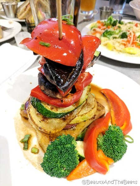 a stack of colorful vegetables inv=cluding squash zucchini red peppers and mushrooms on a white plate