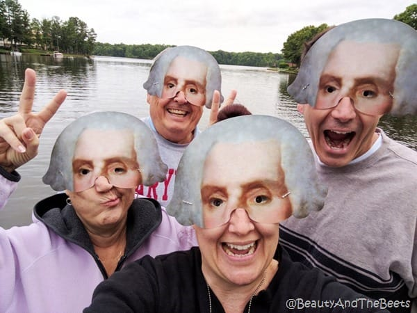 four people wearing half masks of George Washington on a lake with some trees