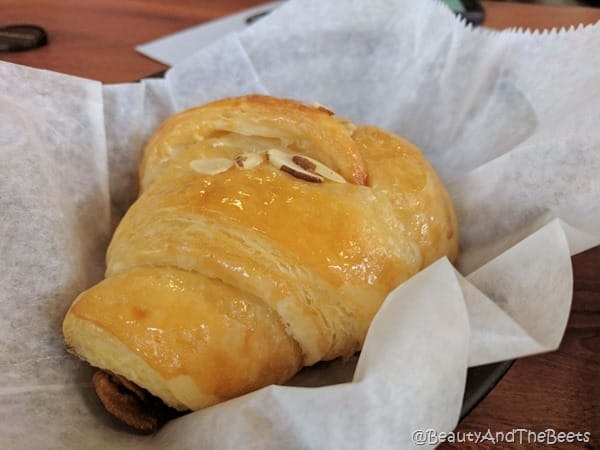 a glazed almond croissant on white parchment paper on a wooden table