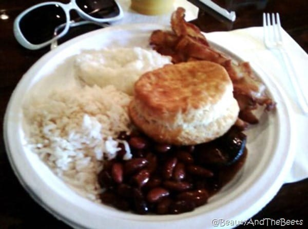 white plate with white rice, red beans, a biscuit and bacon on a table with a pair of white rimmed sunglasses next to the plate