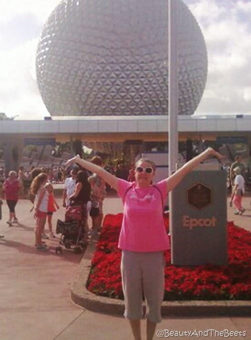 The author in a pink shirt posing big in front the Spaceship Earth ball at Epcot
