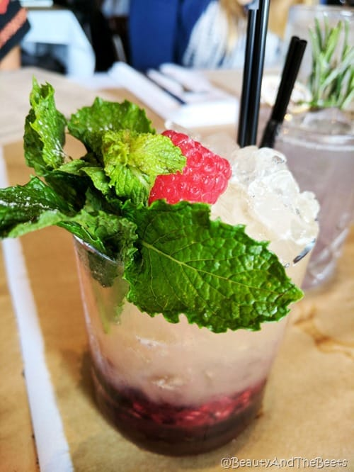 a glss filled with a raspberry puree and crushed ice topped with peppermint leaves and fresh raspberry with a black cocktail straw