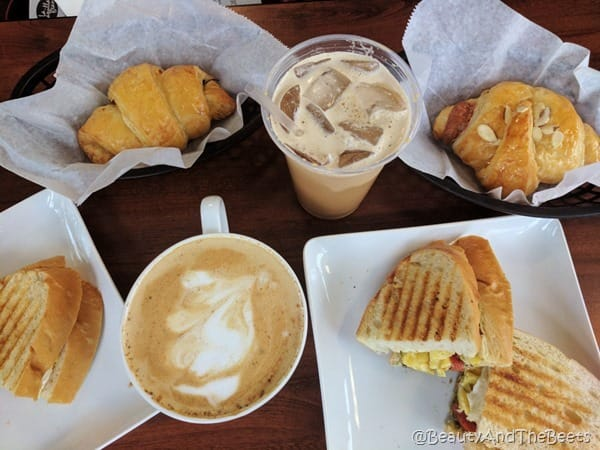 a hot coffee in a white cup with an iced coffee and several sandwiches and pastries on a wooden table