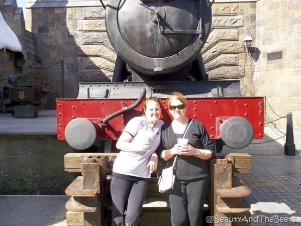 The author and Mother standing in front of a red locomotive train each with a cup of butterbeer