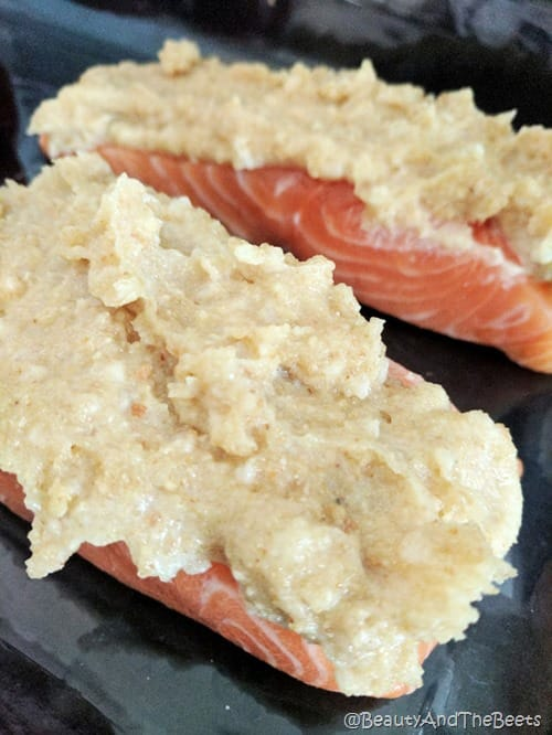 raw salmon filets with a mayo breadcrumb mixture on top on a black background