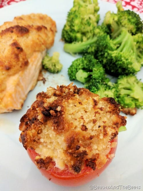 a parmesan crusted tomato on a blue plate with salmon and broccoli in the background