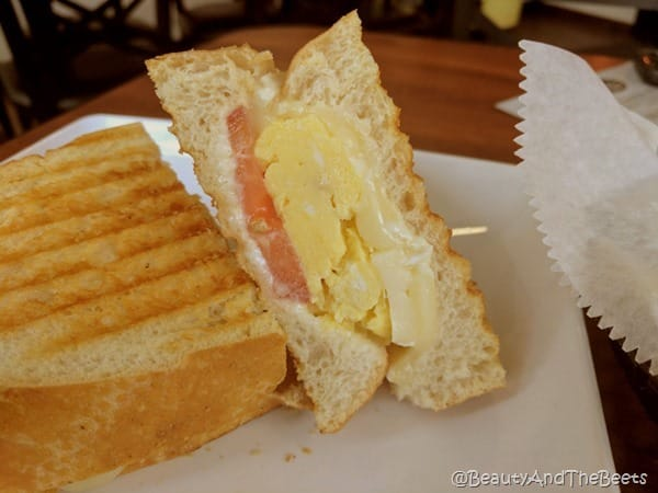 a sandwich with egg and tomato propped up against a half sandwich on a white plate
