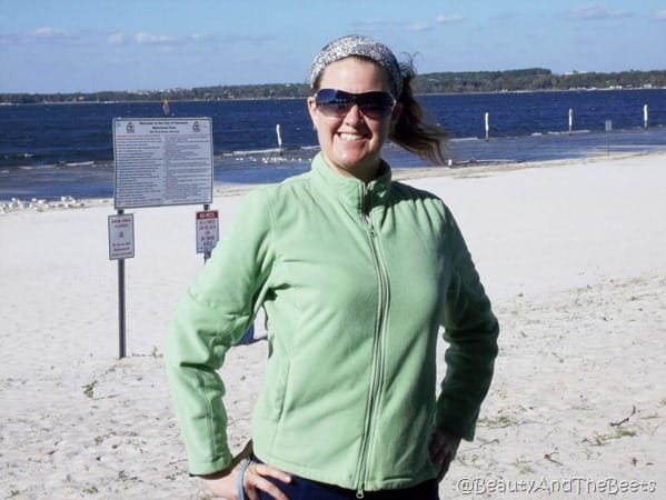 the author in a green sweatshirt on the white sandy beach with the Lake Minneola in the background