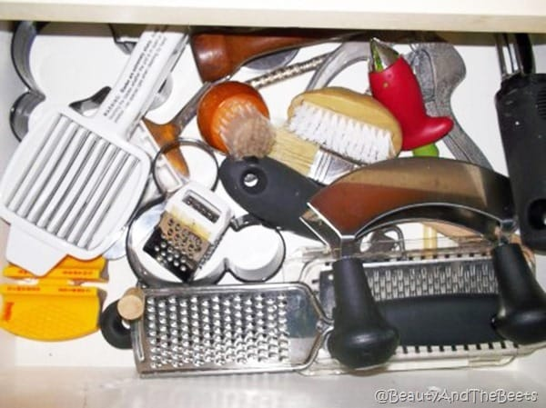 a drawer open filled with kitchen gadgets including potato scrubbers egg rings and mini graters