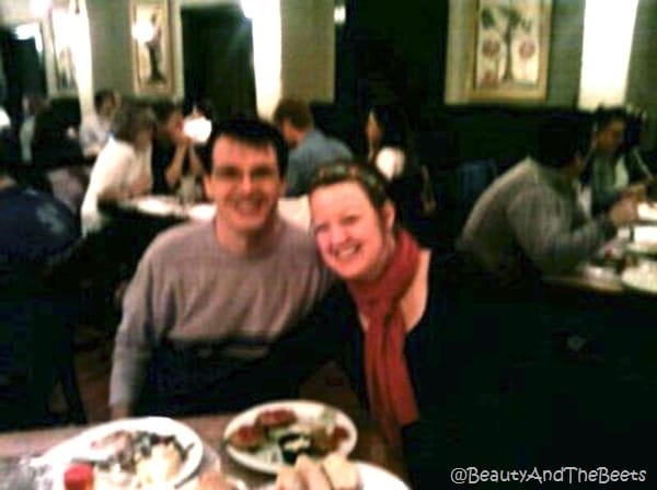 the author with a pink scarf next to Mr Beet at a table in a crowded restaurant