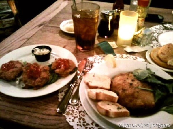 a table full of food on plates with a lit candle and a cup of iced tea