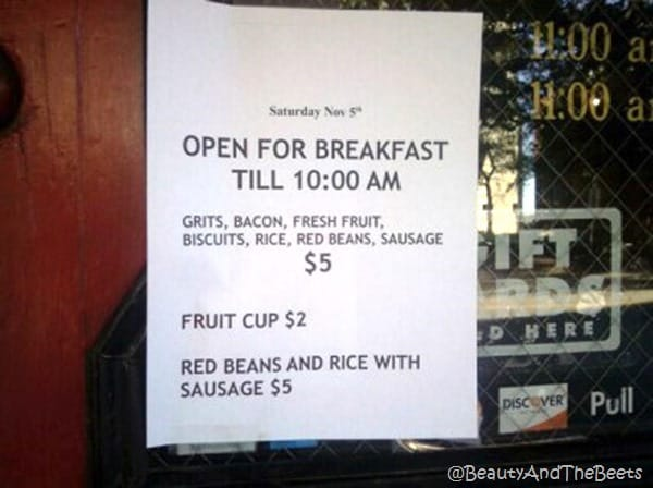 the glass and wodden front door of a restaurant with a white paper listing the breakfast men nu taped to the door