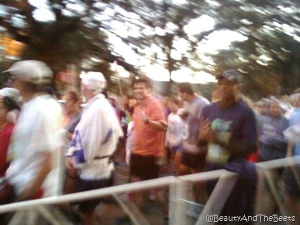 Mr Beet waving to the camera in a blurred picture of runners starting the marathon