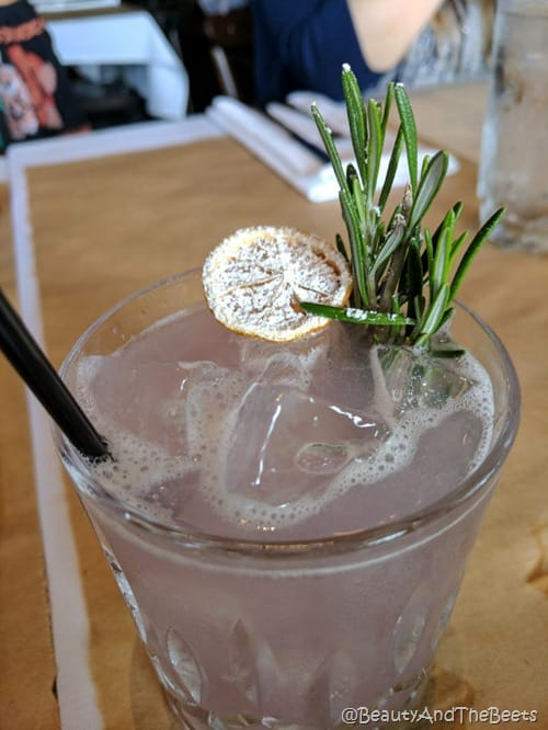 a cocktail glass filled with lavender liquor and vodka with a sugared lemon slice and fresh rosemary sprig with a black cocokatail straw on a wooden tabletop