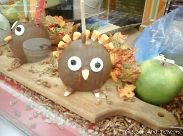 a candy apple covered in chocolate decorated like a turkey with a candy corn mane