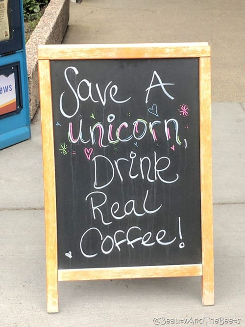 a sandwich board on a street that reads Save a Unicorn Drink Real Coffee