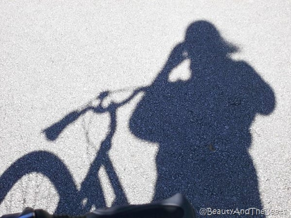 a shadow of a girl and a bicylce on pavement
