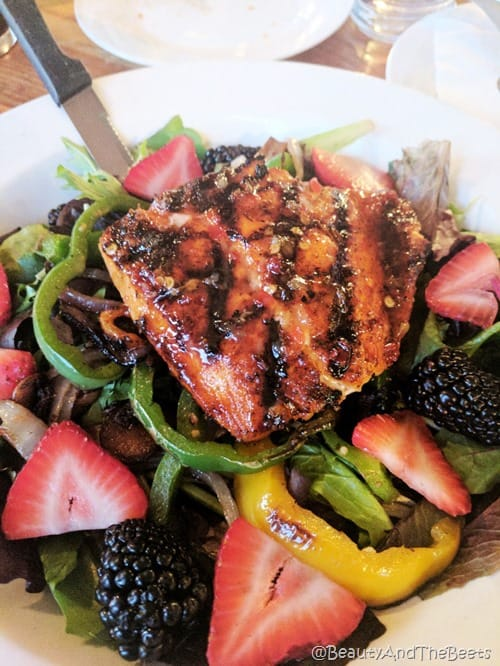 A large piece of glazed salmon over yellow and green peppers, blackberries and sliced strawberries on white plate
