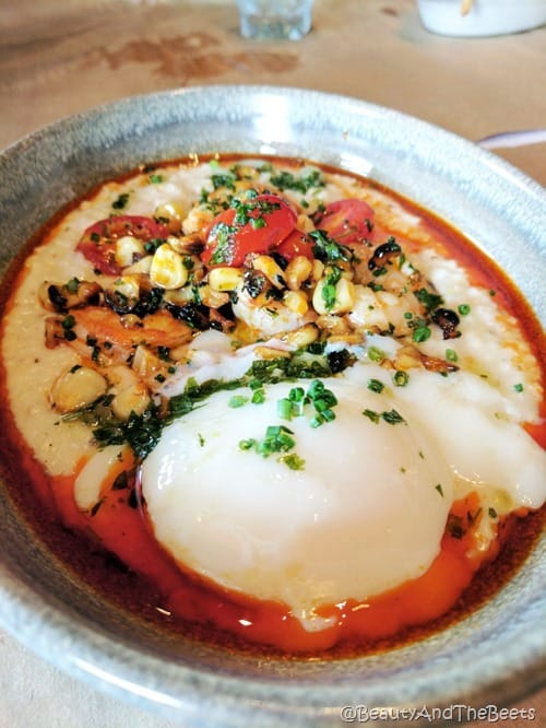 a silver bowl with shrimp, grits, nuts, a poached egg and chopped chives in a red sauce