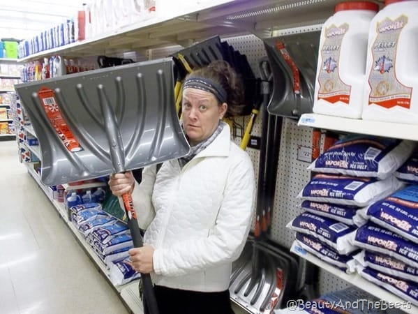 the author looking puzzled holding a big silver snow shovel in the aisle of a market