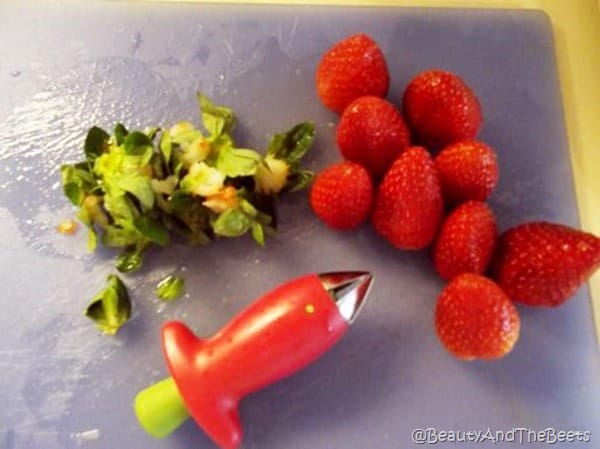 a pile of hulled strawberries next to a pile of hulled stems with the huller on a blue cutting board