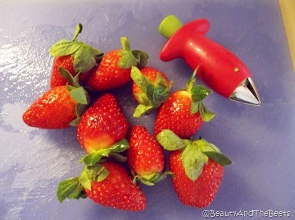 a small bunch of strawberries next to a strawberry huller gadget on a blue cutting board