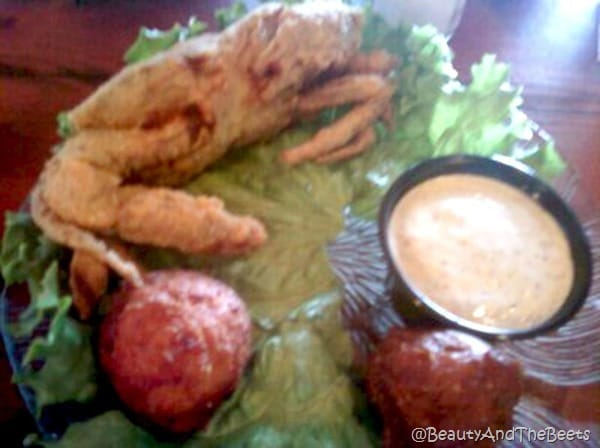 a soft shell crab on a bed of lettuce with red potatoes and a cup of cajun aoli