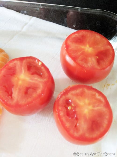 3 ripe red tomatoes in a glass baking dish on a white towel and a black background