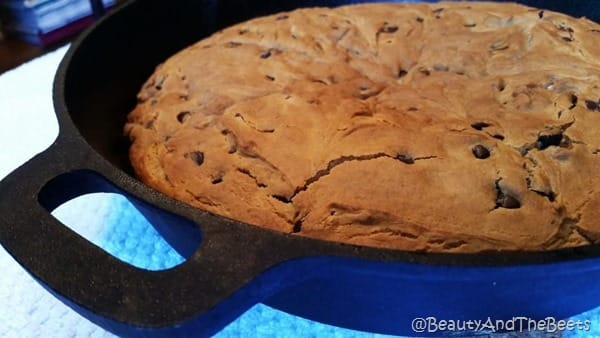 A baked Vegan chocolate chip breakfast cake in a cast iron pan on a blue placemat