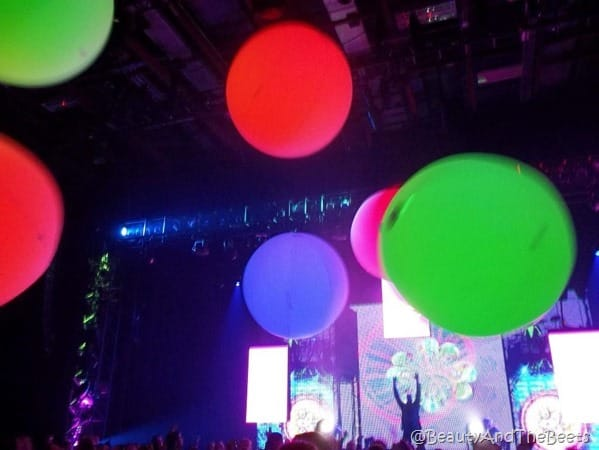 green red blue purple glow balls falling from the ceiling with the Blue Man Group stage in the background