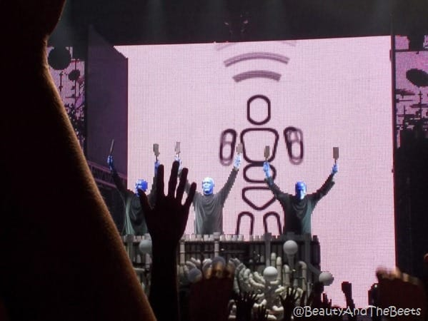 3 Blue Man Group members holding their batons high in the air in front of a giant xylaphone