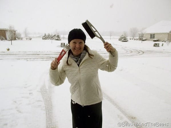 the author wearing a white jacket and black cap playing with a snow scraper and snow brush with a snowy background