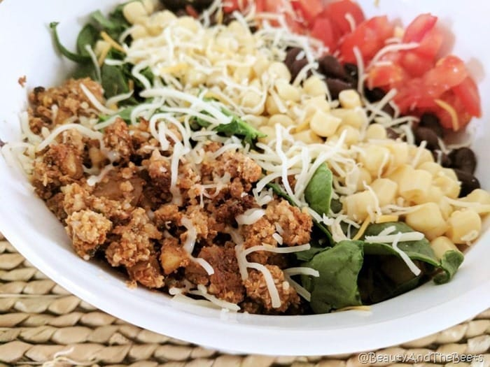 a white bowl filled with rows of cauliflower walnut meat, spinach, white corn, chopped tomatoes and black beans on a bamboo placemeat
