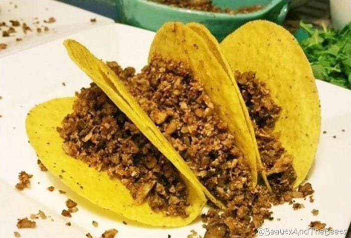 three corn hard shells tacos stuffed with cauliflower walnut crumbles on a white plate