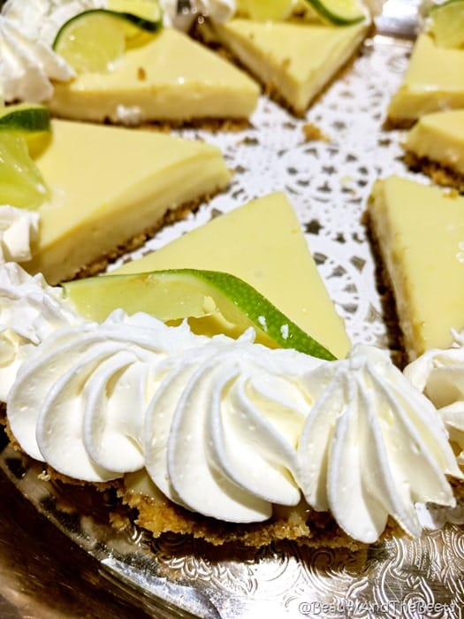 a plate lined with a white doiley with slices of key lime pie topped with whipped cream