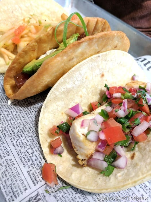a trio of fish tacos in a wonton shell and a flour tortilla on a platter with a newspaper lining