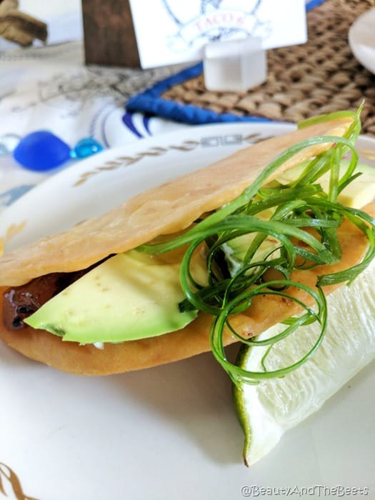 a wonton taco shell filled with greens and tuna ahi on a white plate