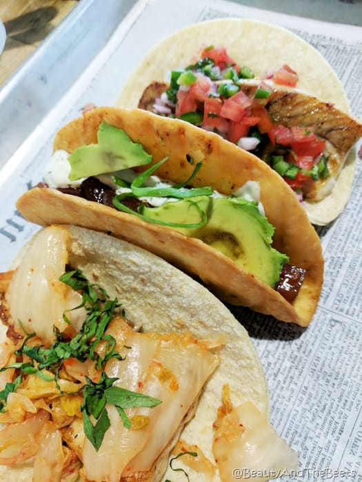a trio of seafood tacos with avocados, mahi mahi and salmon on a tray with a newspaper lining