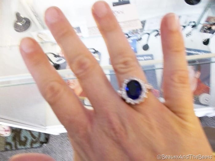 a picture of a hand with a blue diamond encrusted ring