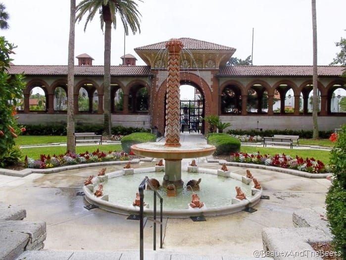 a two tier fountain in a courtyard with spanish tile and a gate with arches