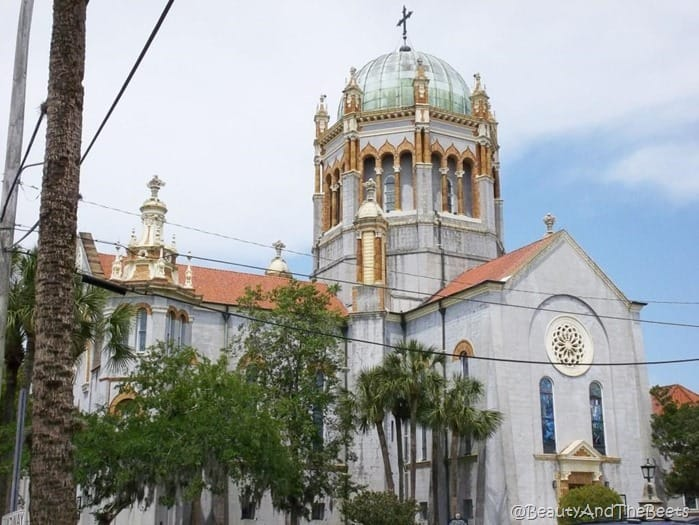 a church with gold features and a spanish tile roof with a giant domed tower
